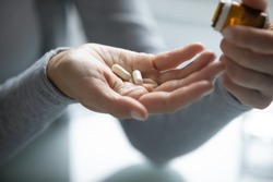 Pharmacy and healthcare. Close up of young female hands holding opened pill bottle and two soft-shelled capsules taking medicine for flu, influenza, painkiller, vitamin complex, oral contraceptives