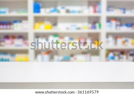 pharmacy counter with blur shelves of drug in the drugstore background