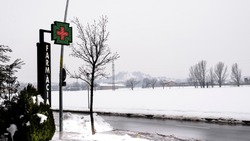 Pharmacy cross , lettering or sign of a pharmacy office in Catalonia, Spain a snowy day.