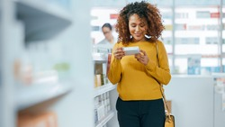 Pharmacy Drugstore: Beautiful Black Young Woman Walking Between Aisles and Shelves Shopping for Medicine, Drugs, Vitamins, Supplements, Health Care Beauty Products with Modern Package Design