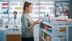 Pharmacy Drugstore: Beautiful Caucasian Young Woman Chooses to Buy Medicine, Drugs, Vitamins, Searches Shelves for the Best Choice. Modern Pharma Store Shelves with Health Care, Beauty Products