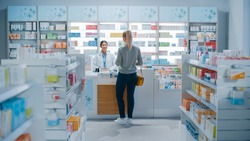 Pharmacy Drugstore: Beautiful Young Woman Buying Medicine, Drugs, Vitamins Stands next to Checkout Counter. Female Cashier in White Coat Serves Customer. Shelves with Health Care Products