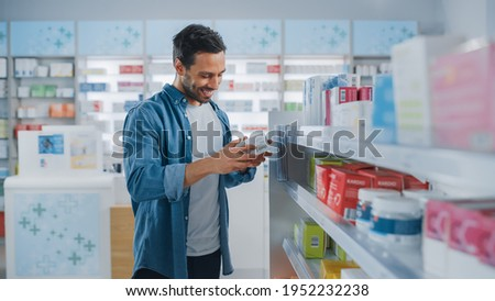 Pharmacy Drugstore: Portrait of Handsome Latin Man Choosing to Buy Medicine Browsing through the Shelf, Successfully finds what he Needs, Smiles Happily. Modern Pharma Store Health Care Products