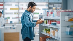 Pharmacy Drugstore: Portrait of Handsome Young Latin Man Searching to Purchase Best Medicine, Chooses between Two Packages of Drugs, Vitamins. Shelves full of Health Care, Wellness, Sport Supplements