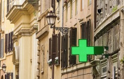 Pharmacy. Medical green cross among the ancient buildings of Rome