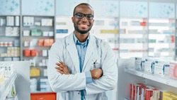 Pharmacy: Professional Confident Black Pharmacist Wearing Lab Coat and Glasses, Crosses Arms and Looks at Camera Smiling Charmingly. Druggist in Drugstore Store with Shelves Health Care Products
