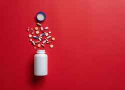 Pharmacy theme,Multicolored pills and capsules with bottle on red background,Copy space for text