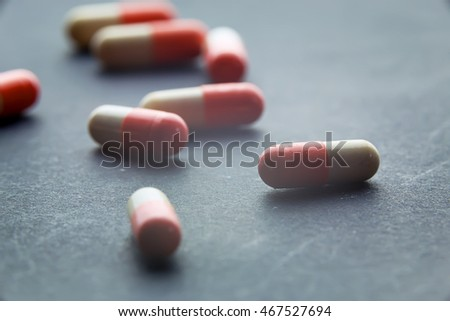 Pharmacy theme Pharmaceutical medicament, cure in container for health. Drug prescription for treatment medication. Heap of red orange white round capsule pills with medicine antibiotic in packages.