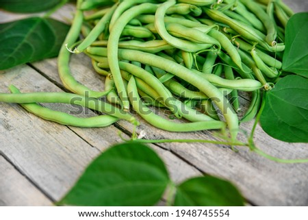 Phaseolus vulgaris, fresh raw common beans, green bush beans with leaves on wooden table Сток-фото ©