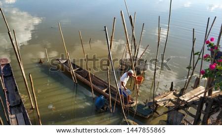PHAYAO, THAILAND - June 22, 2019 : Elderly fishermen are collecting fishing equipment in Kwan Phayao, Phayao Province, Thailand. #1447855865