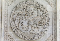 Phenix engraving embossed in stone on the Buddha Temple walls, Gansu province, China.