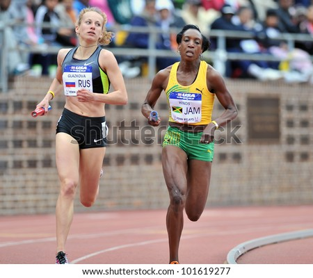 PHILADELPHIA - APRIL 28: Alena Glazkova from Russia (l) tries to overtake a runner from Jamaica in the sprint medley at the Penn Relays April 28, 2012 in Philadelphia.