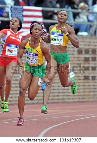 PHILADELPHIA - APRIL 28: Shelly-Ann Fraser-Pryce  from Jamaica (fore) takes the baton for the anchor of a 4x100 USA vs the World heat at the Penn Relays April 28, 2012 in Philadelphia.