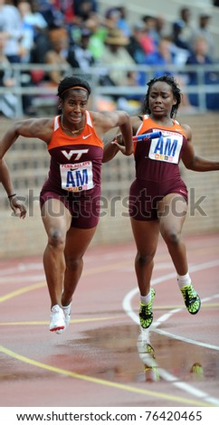PHILADELPHIA - APRIL 28: Zakiya Tyson (r) from Va Tech passes the baton to teammate Ogechi Nwaneri (l) for the anchor leg of their 4x100 relay at the 117th Penn Relays on April 28, 2011 in Philadelphia, PA