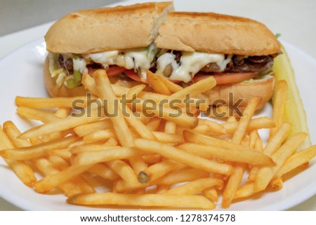 Philadelphia cheesesteak sandwich on a sub bun. Cut in half on white plate with french fries in foreground.