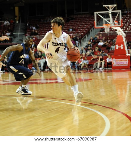 PHILADELPHIA - DECEMBER 12: Temple University guard Juan Fernandez (#4) dribbles  while looking for a teammate on the drive in a game against Akron December 12, 2010 in Philadelphia - stock photo