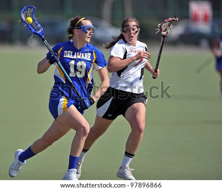 PHILADELPHIA - MARCH 17: Delaware women's lacrosse player Allison Hahn (#19)  runs with the ball on offense as a Temple defenders give chase during a game March 17, 2012 in Philadelphia