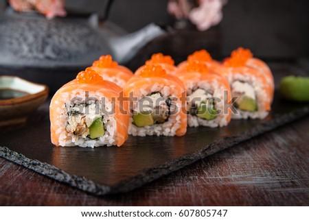 Philadelphia roll sushi with salmon, smoked eel, cucumber, avocado, cream cheese, red caviar. Sushi menu. Japanese food.