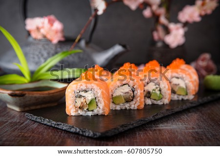 Philadelphia roll sushi with salmon, smoked eel, cucumber, avocado, cream cheese, red caviar. Sushi menu. Japanese food.
