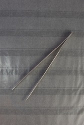 Philatelic tweezer made of stainless steel on a blank page for the album of stamps parallel. top view close-up