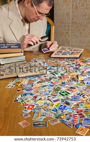Philatelist is examining an old postage stamp with magnifying glass