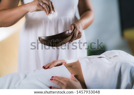 Philippine Psychic Surgery Healer Preparing for Treatment. Using Cotton Ball and Water in Wooden Bowl.