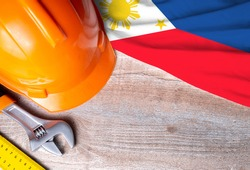 Philippines flag with different construction tools on wood background, with copy space for text. Happy Labor day concept.