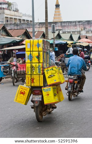 PHNOM PENH, Cambodia - January 2: A man rides a motorcycle overloaded with Cans of cooking oil January 2, 2008 in  Phnom Penh, Cambodia.
