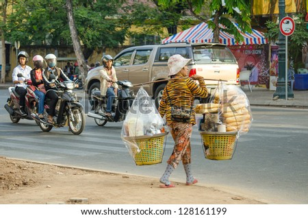 PHNOM PENH, CAMBODIA - JANUARY 2: Unidentified female street seller crosses the road carrying fresh french baguettes on January 2, 2013 in Phnom Penh. Baguettes are popular bread in Cambodia.