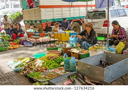 PHNOM PENH, CAMBODIA - JANUARY 1: Unidentified sellers of fruits, vegetables, fish and meat are displaying their merchandise on pavement near Orussey Market on January 1 2013 in Phnom Pehn, Cambodia