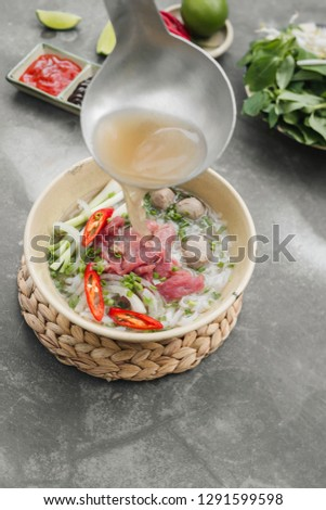 Pho Bo - Vietnamese fresh rice noodle soup with beef, herbs and chili. Stock being poured. Vietnam's national dish.