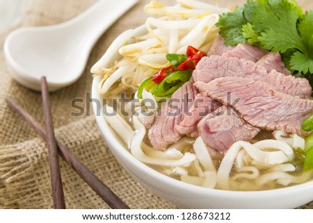 Pho Bo - Vietnamese fresh rice noodle soup with beef, herbs and chili. Vietnam's national dish.