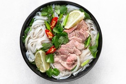 Pho Bo vietnamese soup with beef and rice noodles on a white background, top view, close-up