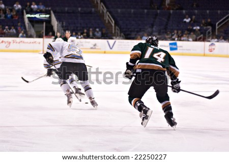 PHOENIX, AZ - DECEMBER 18: Utah Grizzlies forward Tom May (#14) pursues Phoenix Roadrunners wing Ashton Rome (#51) during the ECHL hockey game on December 18, 2008 in Phoenix, Arizona.