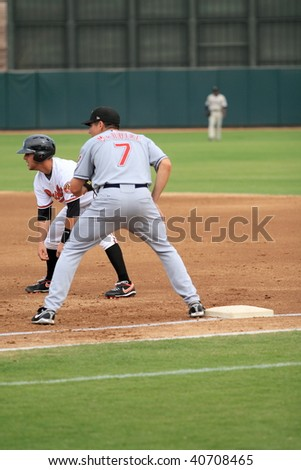PHOENIX, AZ - NOVEMBER 4: Orioles prospect Brandon Snyder leads off first base in an Arizona Fall League game Nov. 4, 2009 in Phoenix, Arizona. Indians prospect Matt McBride (#7) holds Snyder close.