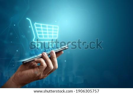 Phone and basket hologram. Online shopping, online store application in a smartphone. Digital Marketing Online Foto stock ©