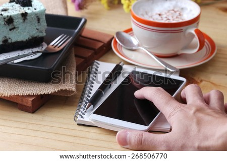 phone and pen notebook with coffee up and mint cake on wooden table #268506770