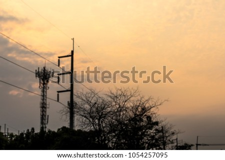 Phone Antenna High-voltage black poles, blurry and sunset light, yellow orange early in the morning. #1054257095