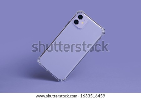 Photo of  Phone case mockup isolated on purple background. iPhone 11 in clear silicone case falls down back view