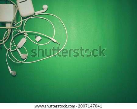 phone charger and white headphones Placed on a green background with vignettes, vintage style, copy space. Foto stock ©