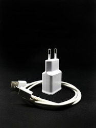 Phone charger. Smartphone chargers with multiple positions. The charging port cable is white. Phone charger is one of the mobile phone accessories. Smartphone charger on black background