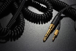Phone connectors. Jack connectors and audio cables for headphones and microphones on black background
