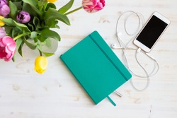 Phone, earbuds, journal and tulips on white table