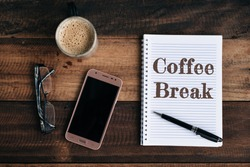 phone, glasses, coffee mug and notebook with COFFEE BREAK word on wooden table. coffee break conceptual