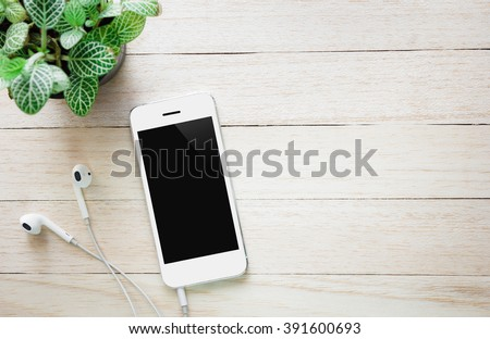 Phone headsets and tree on a wooden table.