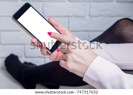 Phone in hand, finger click on blank screen. Woman sitting at the wall in the room and browsing the mobile phone. Online shopping, viewing messages, sending messages. #747317632