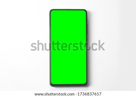 Photo of  Phone mobile telephone with a vertical green screen in tram chroma key smartphone technology cell phone on white background isolate