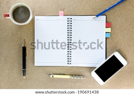 phone,notebook, pen and cup of coffee on work table top view