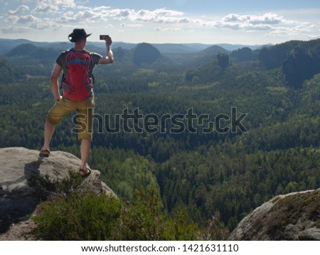 Phone photographer. Man tourist on the edge take phone pictures.  Hker in leather hat, t-shirt, shorts and sandals with red backpack on back.