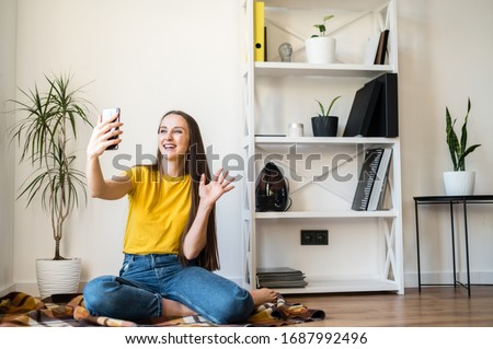 Phone video call. A young woman communicates via video, zoom. She is sitting on the floor in a Scandinavian style room.